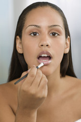 Young woman applying lip gloss