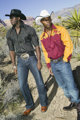 Young men in cowboy outfits posing for the camera