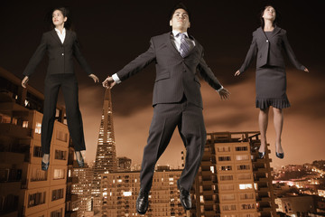 Businesspeople floating above the city