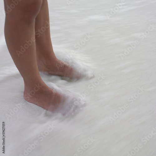 Woman's feet in the waves at the beach