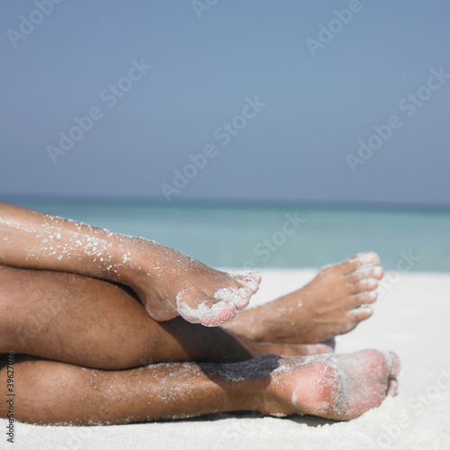 Couple's legs on the beach