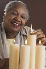 Senior woman lighting candles