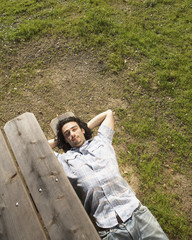 Man relaxing on picnic bench