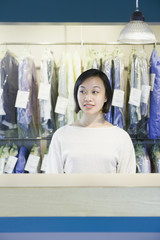 Asian drycleaner standing behind counter