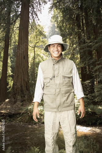 Explorer smiling in forested area
