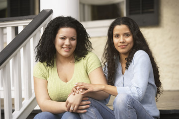 Hispanic sisters sitting on the porch holding hands