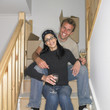 Couple having a drink on stairs in new house