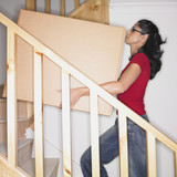 Woman carrying box up stairs in new house