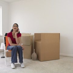 Woman sitting next to boxes in new house
