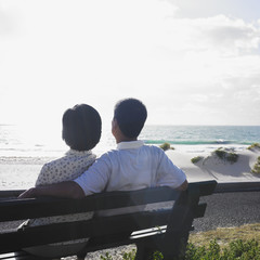 Couple sitting on a bench at the beach