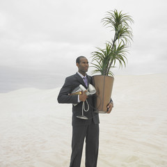 African businessman carrying plant and lamp in the desert
