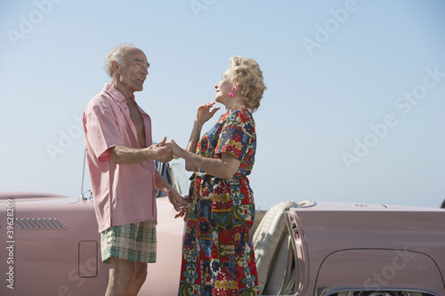 Senior couple next to a pink convertible