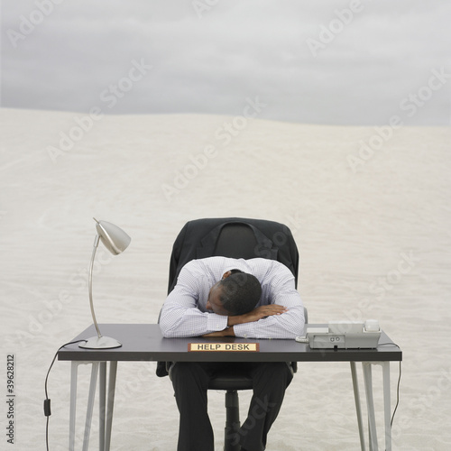 African businessman resting his head on help desk in the desert
