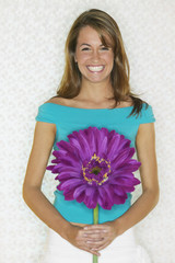 Young woman smiling and holding large flower