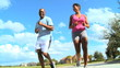 African American Couple Jogging on Suburban Road