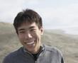 Asian man smiling at the beach