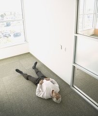 Middle-aged businessman lying on office floor