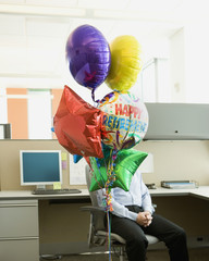 Bunch of retirement balloons in front of a businessman in a cubicle