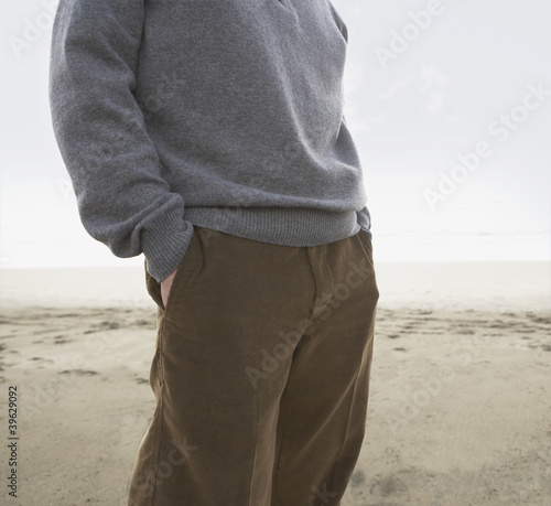 Man standing on the beach with his hands in his pockets