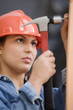 Hispanic female construction worker hammering a nail