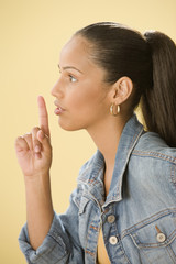 Studio shot of a female Dominican teenager putting index finger to lips