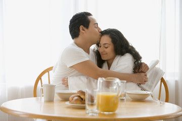 Hispanic couple hugging at the breakfast table