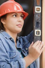 Hispanic female construction worker using a level