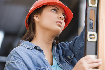 Hispanic female construction worker using a level