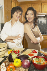 Asian mother and grown daughter preparing dinner