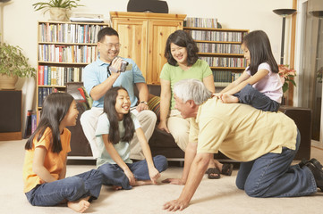 Three generations of an Asian family playing in the livingroom