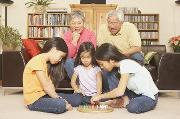 Three young Asian sisters playing chinese checkers while grandparents watch