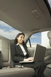 Businesswoman working in the backseat of a car