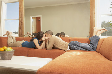 Young Hispanic couple lying on the sofa kissing