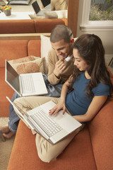 Young Hispanic couple sitting on sofa with laptops