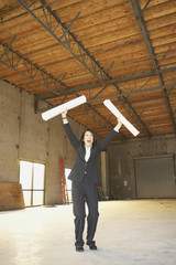 Businesswoman cheering in empty warehouse with blueprints
