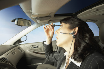 Businesswoman driving and putting on makeup