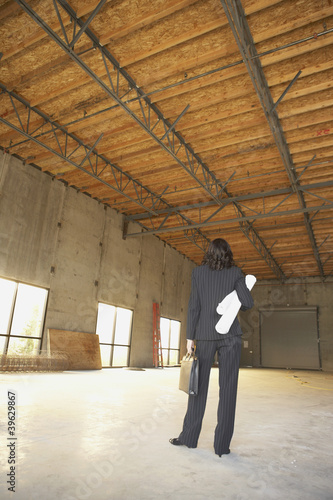 Businesswoman standing in empty warehouse with blueprints