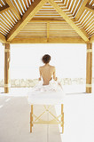 Woman sitting up on massage table outdoors