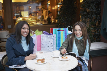 Two woman eating at a cafe with shopping bags