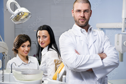 Male dentist with assistant and smiling patient at dental clinic