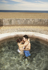 Couple hugging in hot tub outdoors at beach resort