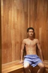 Hispanic man sitting in sauna