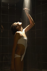 Woman in bathing suit rinsing in shower