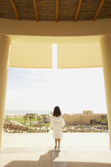 Woman in bathrobe outdoors at resort hotel