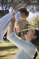 Hispanic mother holding baby up outdoors