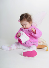 The small beautiful girl in pink clothes on a white background