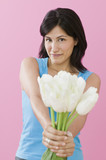 Studio shot of Hispanic woman holding tulips