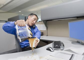Asian businessman spilling coffee on desk
