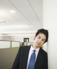 Businessman with eyes closed leaning on wall