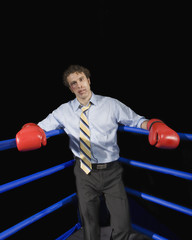 Businessman in corner of boxing ring with black eye